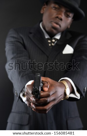 Retro african american mafia man wearing striped suit and tie and black hat. Shooting a with gun. Studio shot.