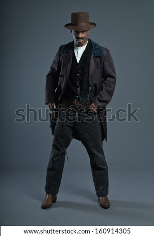 Retro Afro america western cowboy man with mustache. Taking his gun. Wearing brown hat. Cool tough guy. - stock photo