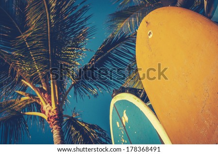 Retro Aged Style Photo Of Surf Boards And Palm Trees - stock photo