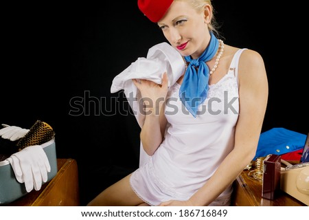 Retro Airline Stewardess or Flight Attendant Removing Her Shirt After Work.