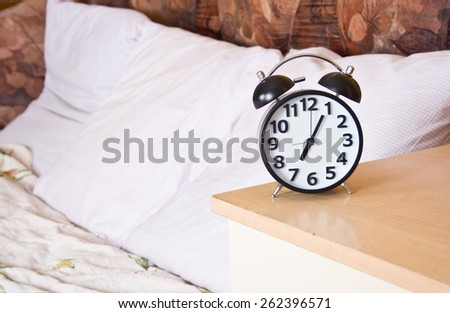 Retro alarm clock and bed background. - stock photo
