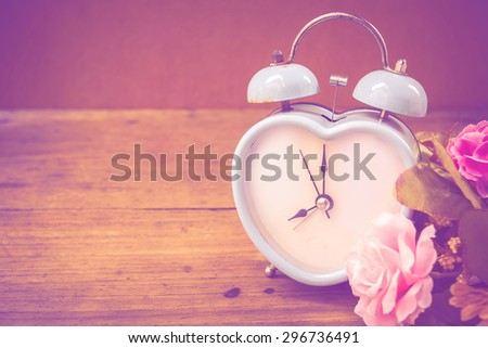 retro alarm clock and watering can with flowers on wooden rusty background,vintage color tone.