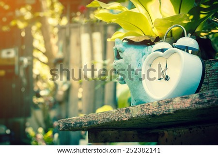 retro alarm clock in garden with sun light - stock photo