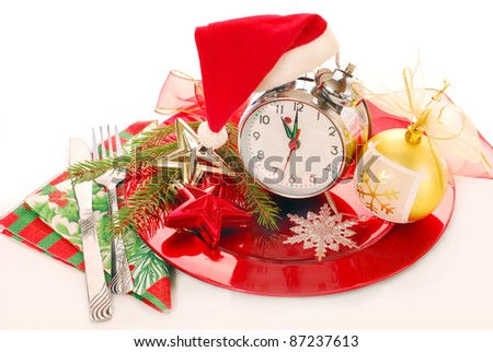 retro alarm clock in santa hat on red plate with christmas decoration isolated on white