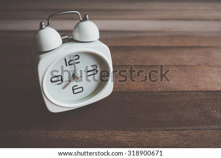 Retro alarm clock on old wooden background. Vintage effect. - stock photo