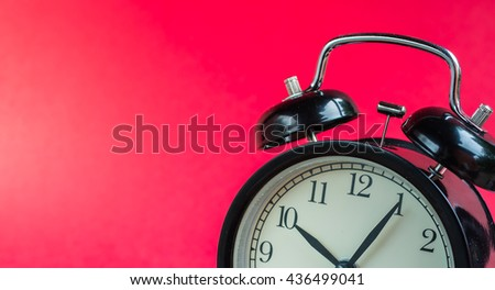 Retro alarm clock on red background,Clock concept background,clock with copy-space,ten o'clock and five minute