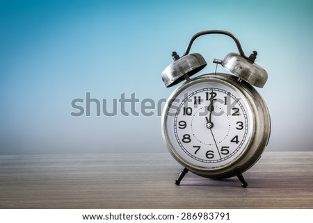 retro alarm clock on table in vintage style - stock photo