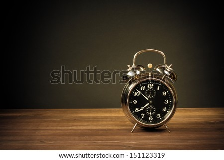 Retro alarm clock on table on dark background - stock photo
