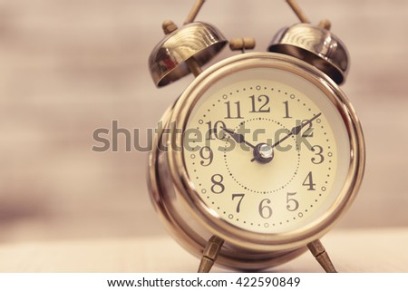 Retro alarm clock on table on office background - stock photo