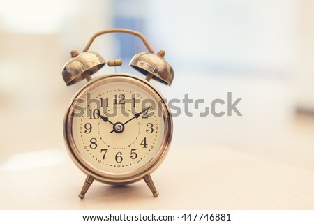 Retro alarm clock on table on office background