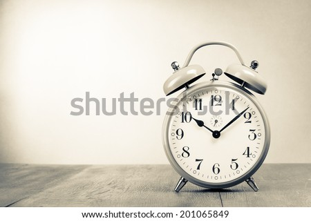 Retro alarm clock on table. Vintage style sepia photo - stock photo