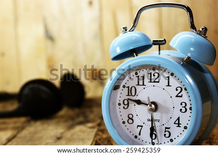 Retro alarm clock on the old wood background