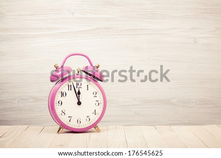 Retro alarm clock on wooden desk - stock photo