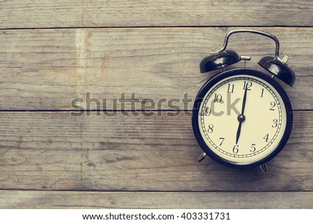 Retro alarm clock on wooden table, vintage style - stock photo