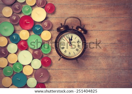 Retro alarm clock with candles on wooden background