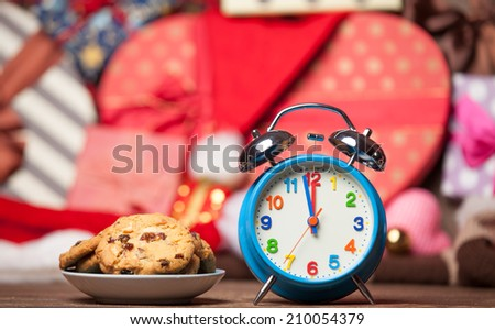 Retro alarm clock with cookie on a table. Photo in retro color image style - stock photo
