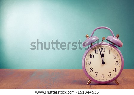 Retro alarm clock with five minutes to twelve o'clock - stock photo