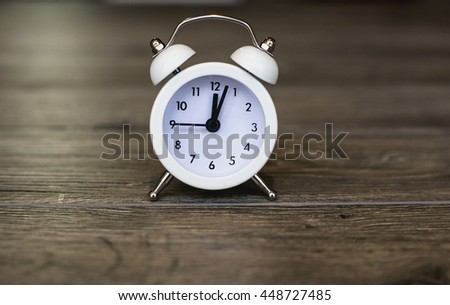 Retro alarm clock with five minutes to twelve o'clock. Old style filtered photo - stock photo