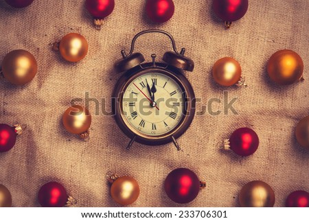 Retro alarm clock with gold and red balls on jute background. - stock photo