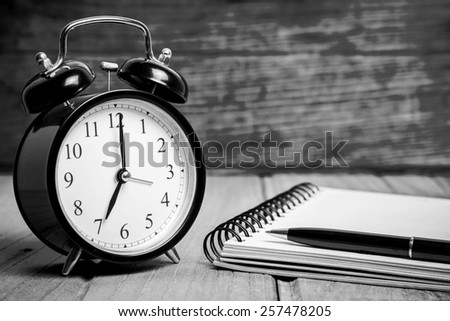 Retro alarm clock with notebook and pen, Black and white tone  - stock photo