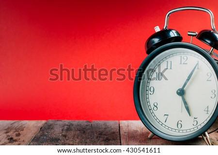Retro alarm clock with 5 o'clock five minutes. Vintage style colour. - stock photo
