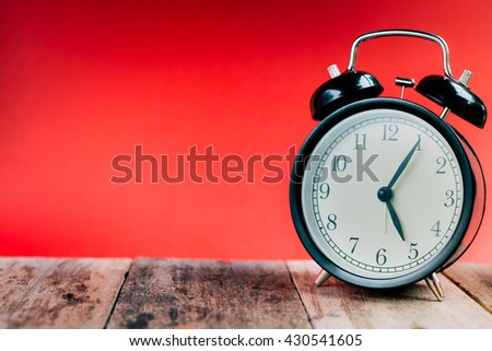 Retro alarm clock with 5 o'clock five minutes. Vintage style colour. Black alarm clock. Retro alarm clock. clock concept. Clock with space. clock on wood and red background. - stock photo