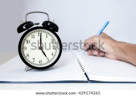 Retro alarm clock with retro colored in white background, white background with retro alarm clock on table, Big old vintage alarm clock with bells, painted white wooden background - stock photo
