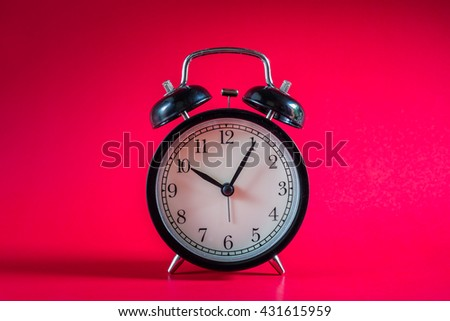 Retro alarm clock with Ten o'clock and five minute on red background. - stock photo