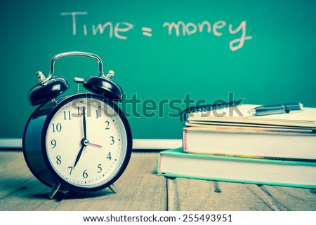 Retro Alarm clock with text book and green board background, vintage tone  - stock photo