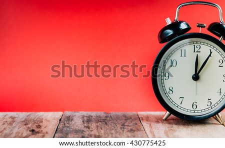 Retro alarm clock with Twelve o'clock and five minutes. Vintage style colour.clock concept.  - stock photo