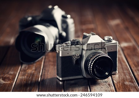 retro and dslr camera on wooden table - stock photo