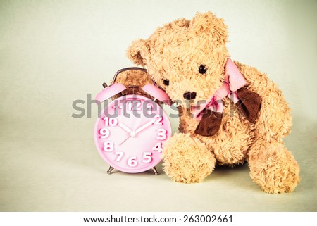retro and vintage style of the Old fashioned alarm wake up clock and cute brown bear doll - stock photo