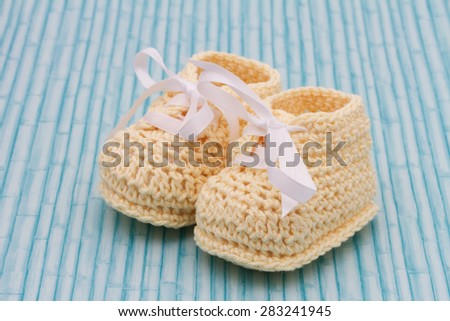Retro Baby Booties, Pale Yellow Baby Booties on a grunge wood background - stock photo