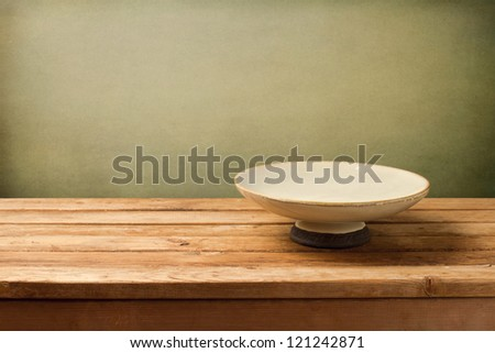 Retro background with plate on wooden table over grunge background