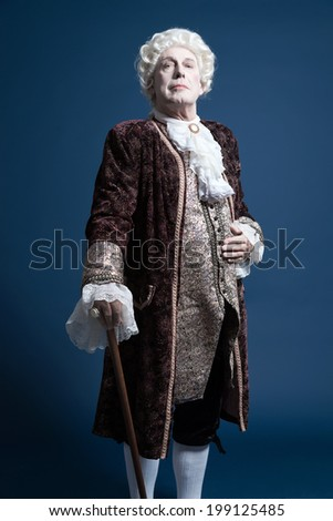 Retro baroque man with white wig standing with walking stick arrogant looking. Studio shot against blue. - stock photo