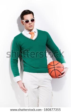 Retro basketball fashion man wearing white sunglasses a green sweater orange tie and white shorts. Studio shot against white wall. - stock photo