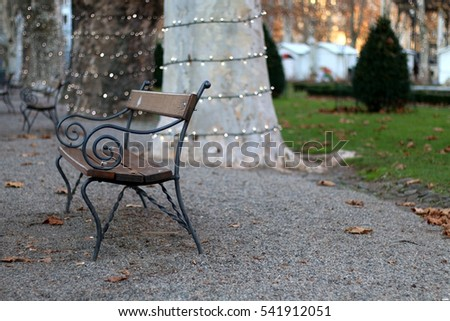 Retro bench in a park, with fairy lights on the trees. Selective focus. In Zagreb, Croatia.