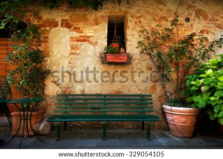 Retro bench outside old Italian house in a small town of Pienza, Italy. Plants decorations, vintage - stock photo