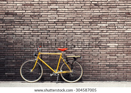 Retro bicycle on roadside with vintage brick wall background - stock photo