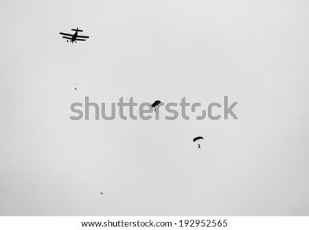 retro  biplane with skydivers in black and white - stock photo