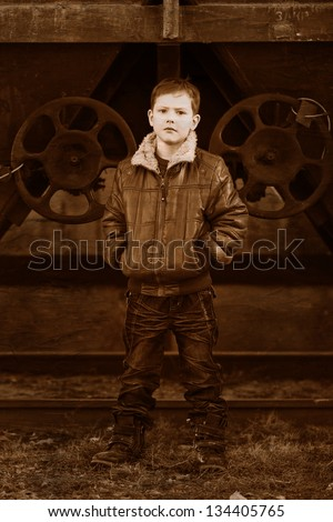 Retro black and white photo of sepia boy blonde tramp in a brown jacket, crumpled jeans on the street near the railway wagons - stock photo