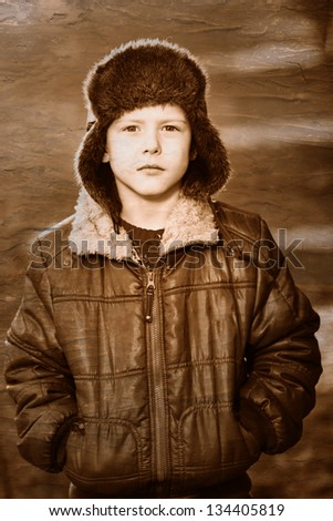 Retro black and white photo of sepia boy in brown jacket and fur hat on street on blue abstract background - stock photo
