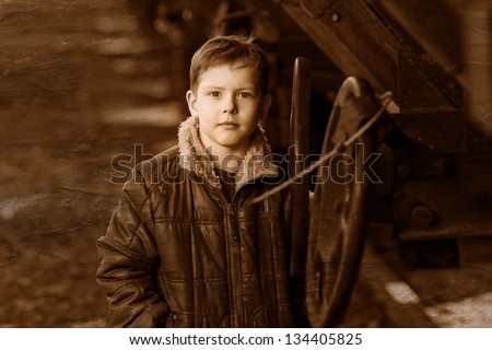 Retro black and white photo of sepiaboy homeless large portrait in brown jacket on street rail car look up - stock photo