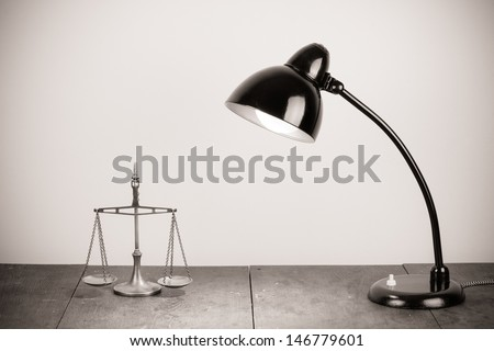 Retro black lamp and scales on old table - stock photo