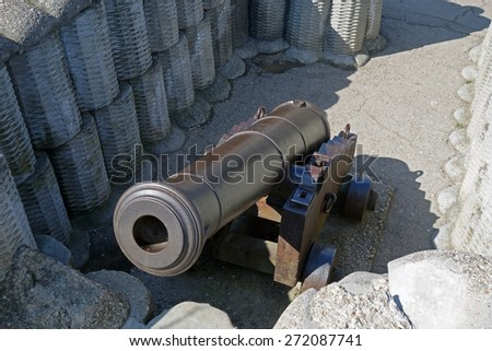Retro black metal gun in the fortification  - stock photo