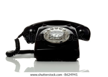 Retro black telephone on a white surface with reflection. - stock photo