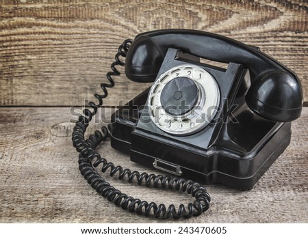 Retro black telephone on wood background from the Soviet Union - stock photo