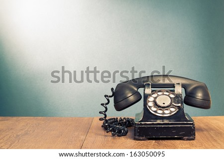 Retro black telephone on wooden table in front gradient background - stock photo