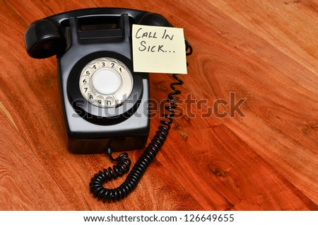 Retro black telephone with reminder note to call in sick - stock photo