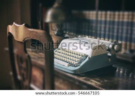 Retro blue typewriter standing on wooden table. Horizontal indoors shot